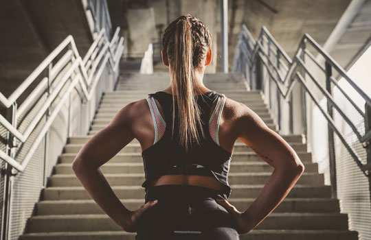 Female with athletic build looking at stairs with hands on hips